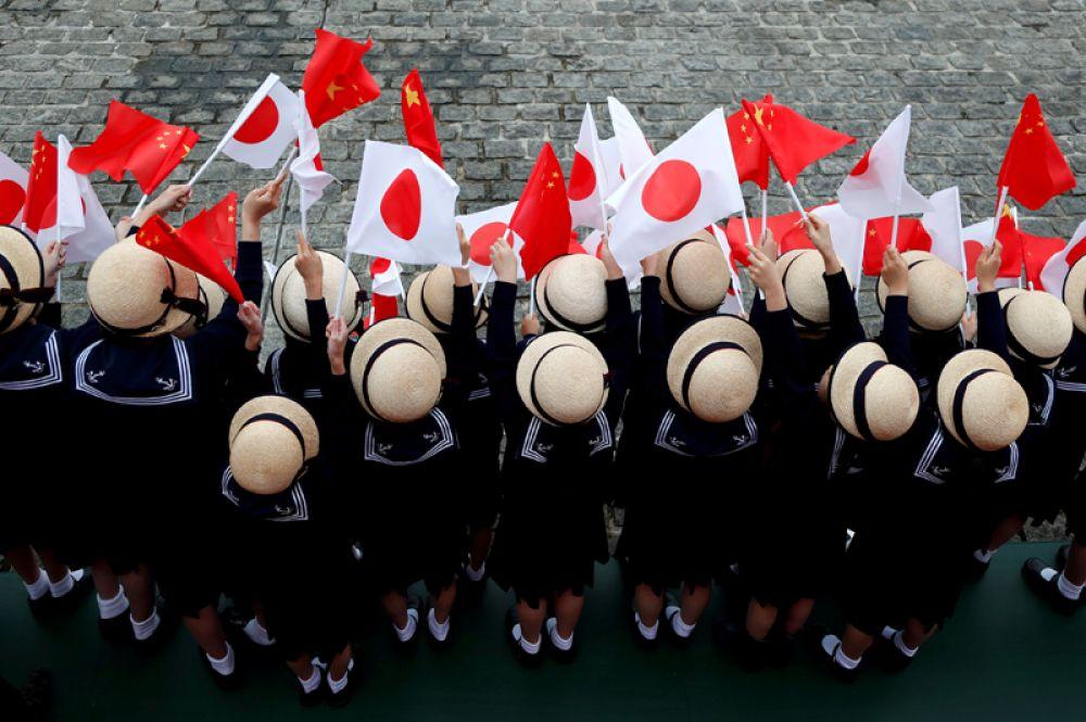 Воспитанники детского сада с национальными флагами в руках приветствуют премьер-министра Японии Синдзо Абэ и китайского премьера Ли Кэцяна перед началом их двусторонних переговоров в Токио, Япония.