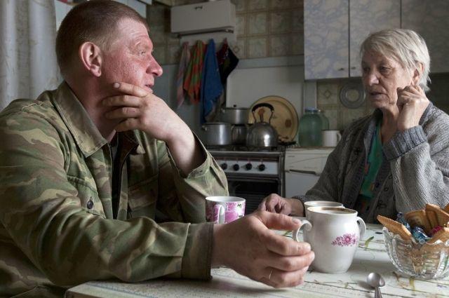 Работник службы соцподдержки беседует с пенсионеркой.