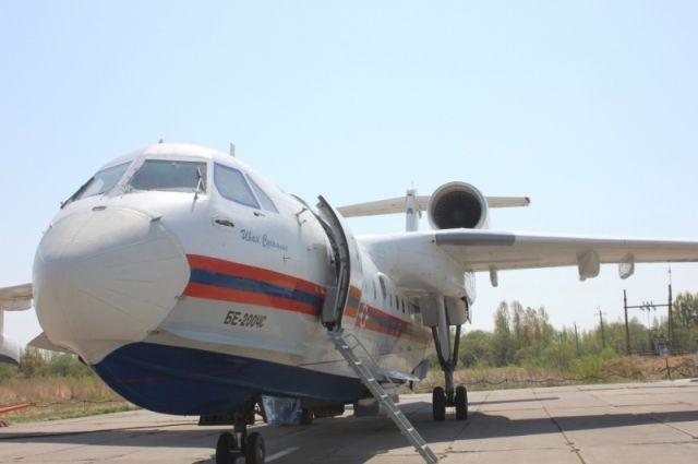 Самолёт сбросил воду по кромке лесного пожара.