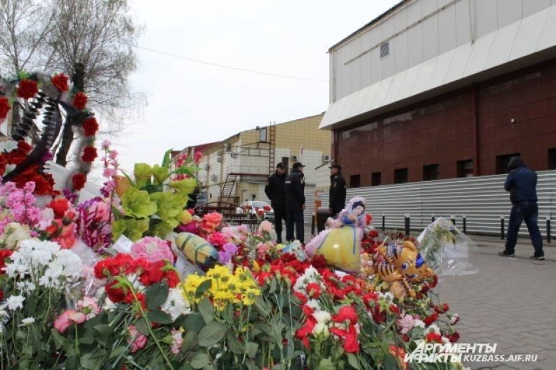Люди продолжают нести к стихийному мемориалу возле сгоревшего ТЦ цветы и игрушки.