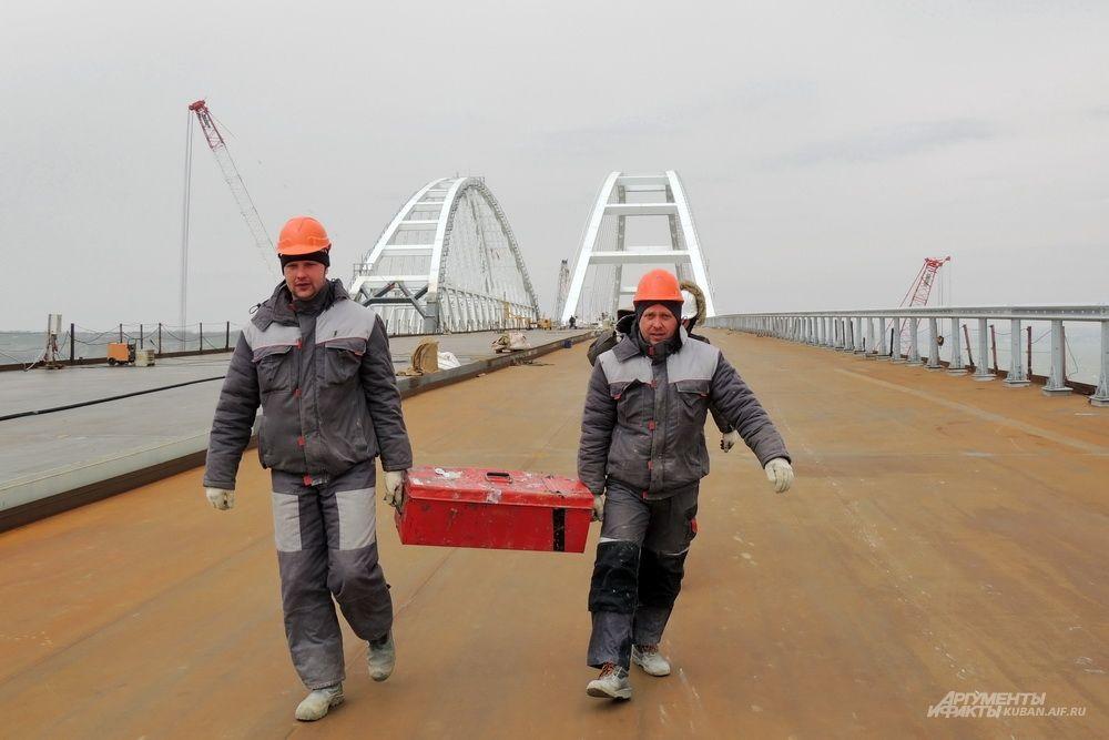 Строители с ящиком инструментов на фоне арок моста. 23 марта 2018 года.