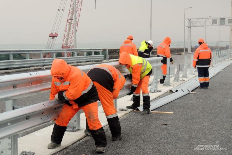 Строители монтируют барьерные ограждения. 23 марта 2018 года.