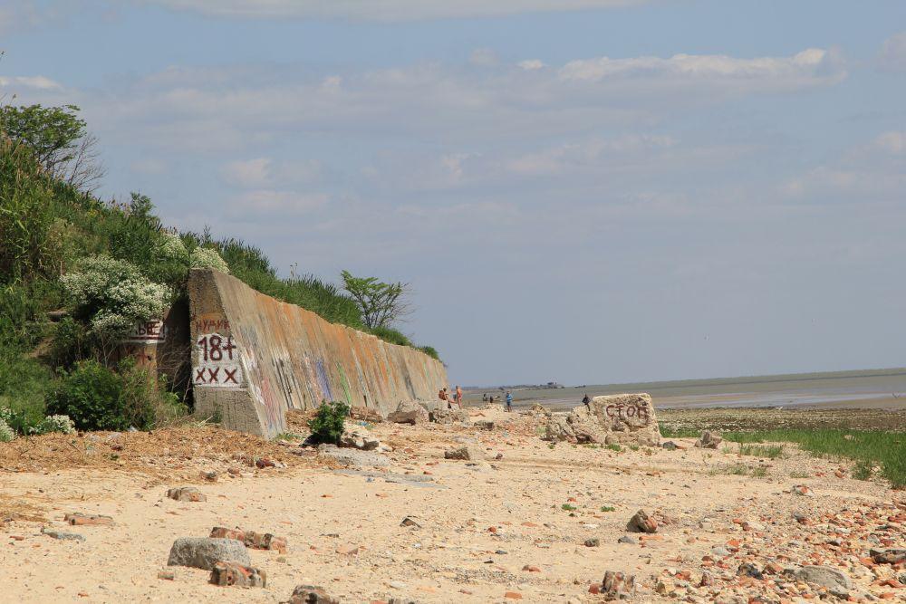 Остатки подпорной стены, которая должна защищать дома на горе. Теперь здесь нудистский пляж, о чем красноречиво написано на стене. Жители не в восторге от такого соседства.