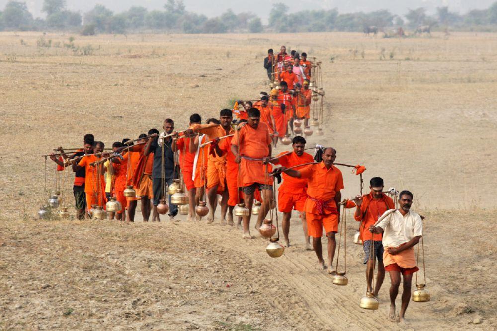 Шиваиты несут металлические горшки, наполненные святой водой из реки Ганг, Аллахабад, Индия.