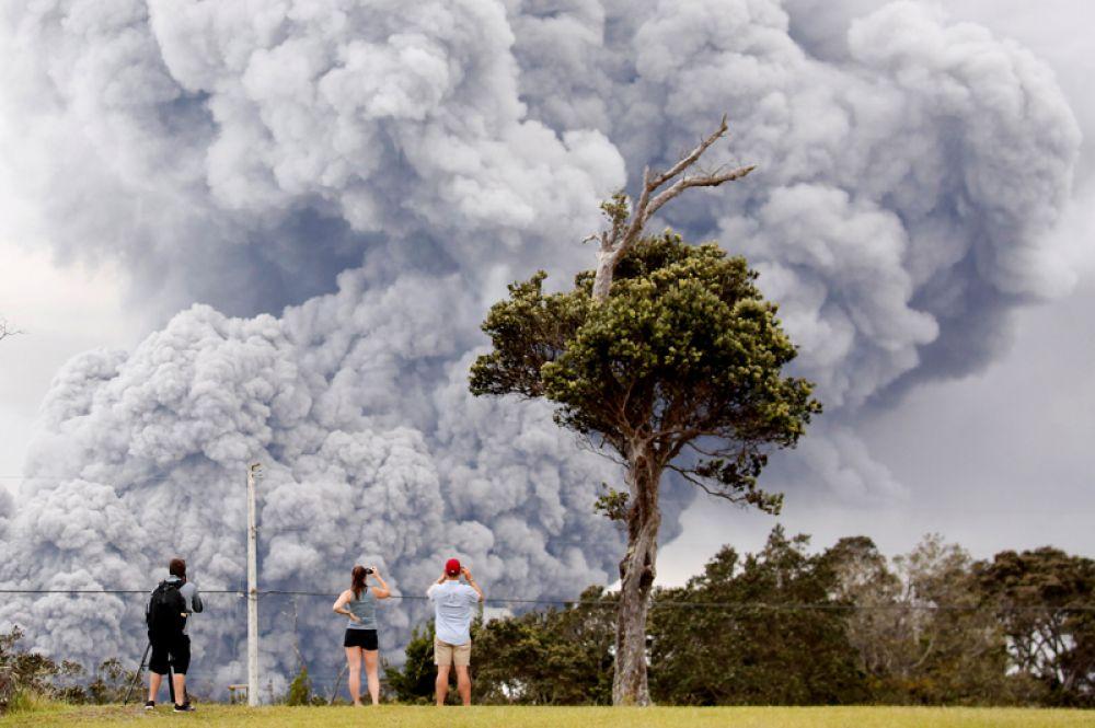 Люди наблюдают за извержением пепла из кратера вулкана Килауэа на Гавайях, США.