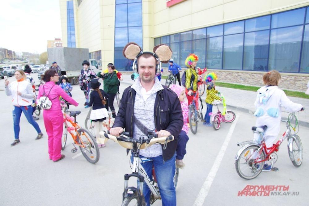 Участник карнавала на велосипедах нарядился в медведя.