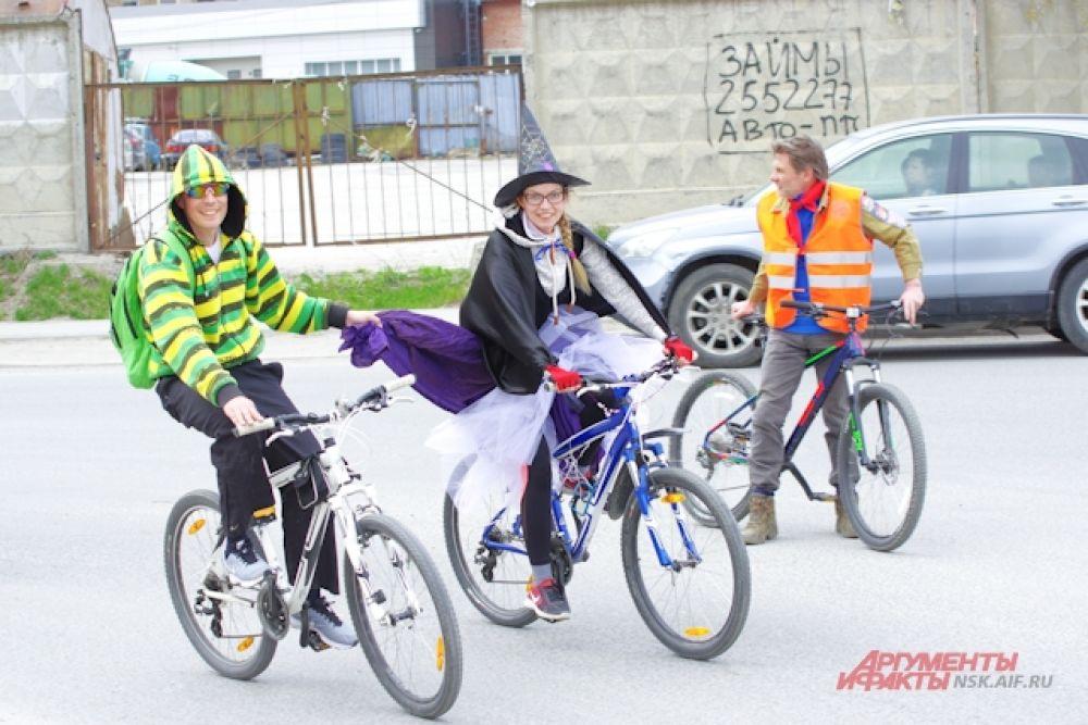 Девушка в костюме ведьмы приехала на велокарнавал в окружении двух кавалеров.