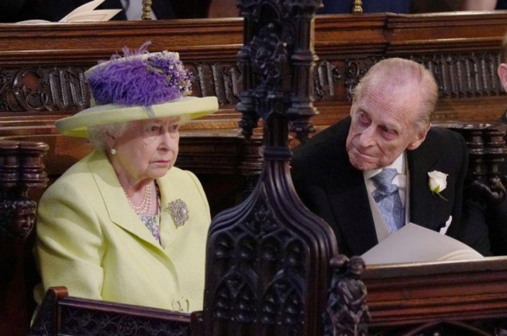 Королева Елизавета II и ее супруг, принц Филипп, в ложе каплицы святого Георгия. Королева традиционно выбрала желтый (свой любимый) цвет для торжеств.