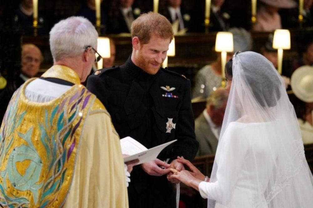 Меган Маркл и принц Гарри дают торжественные обещания и клятвы перед алтарем. Принц Гарри - бунтарь Кенсингтонского дворца. нарушил традицию своего отца и надел кольцо после клятвы, хотя ни его отец, ни старший брат, колец не носили.