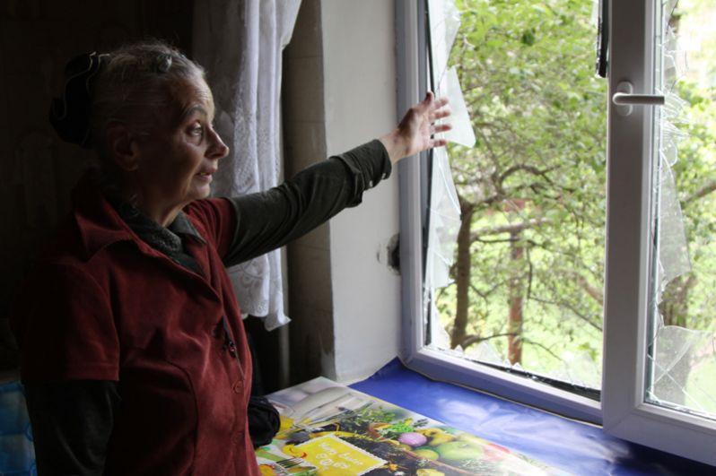 Жительница демонстрирует разбитое окно в жилом доме, пострадавшем в результате обстрела, в поселке Горловка Донецкой области.