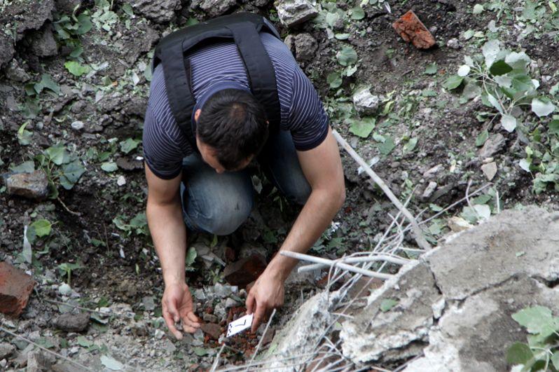 Представители наблюдательной группы СЦКК «Горловка» собирают осколки от снарядов.