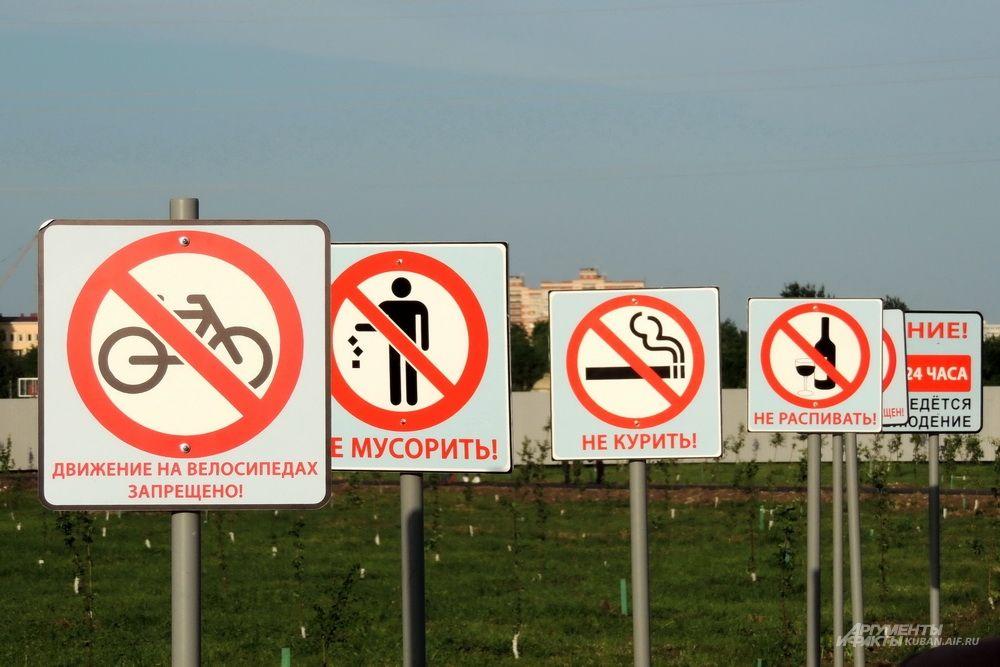 Таблички на входе в парк предупреждают посетителей о правилах поведения.