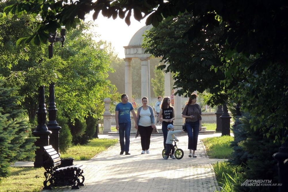 Во вновь открытый парк люди проходят целями семьями.