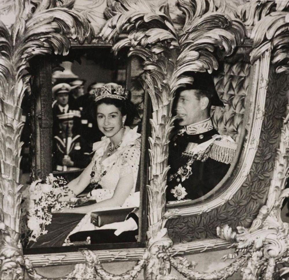 Королева Елизавета ехала в золотой карете, запряженной восьмеркой лошадей. Поверх платья на ее плечах красовалась пятиметровая бархатная мантия, отороченная горностаем, а на голове — корона Георга IV.