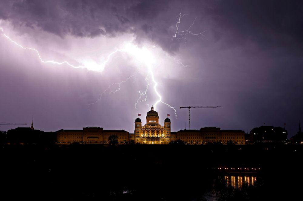 Молния в небе над Федеральным дворцом в Берне, Швейцария.