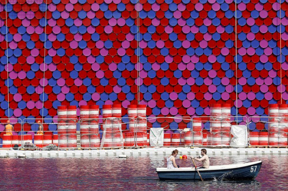 Рабочие возводят инсталляцию «Мастаба», изготовленную из пластиковых бочек, на озере Серпентайн в Лондоне, Великобритания.