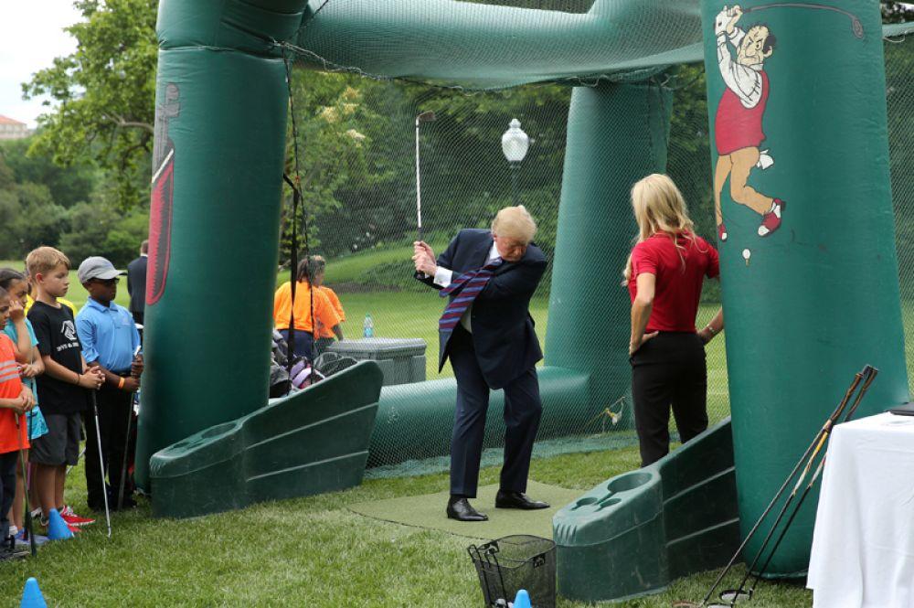 Президент США Дональд Трамп играет в гольф во время празднования Дня спорта и фитнеса в Белом доме, Вашингтон.