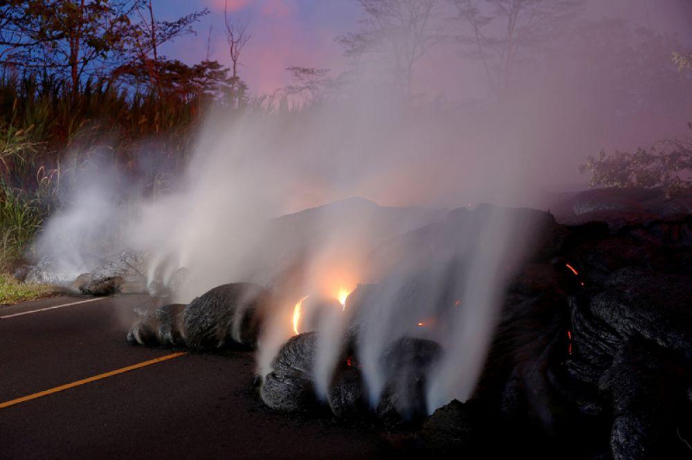 Вулканические газы и потоки лавы из извергающегося вулкана Килауэа около Пахоа, Гавайи.