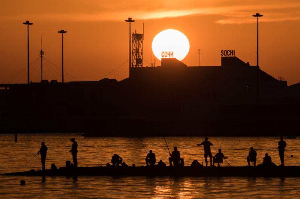 Рыбаки во время заката на центральной набережной в Сочи.