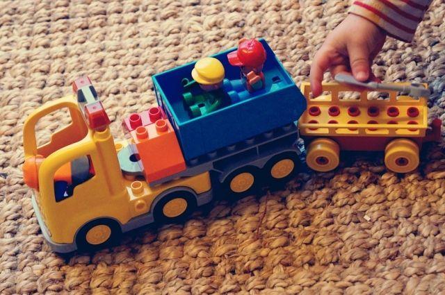 Ребенок просунул палец в игрушечную машинку.