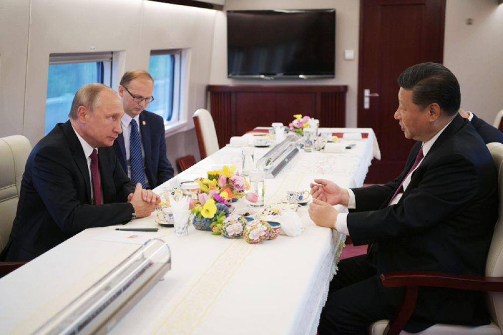 Президент РФ Владимир Путин и председатель КНР Си Цзиньпин едут на электропоезде в Тяньцзинь.