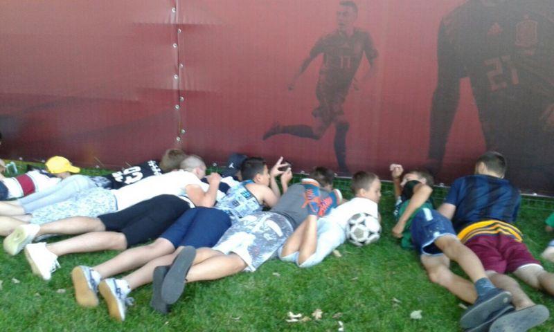 Мальчишки смотрят на тренировку через обшивку стадиона.