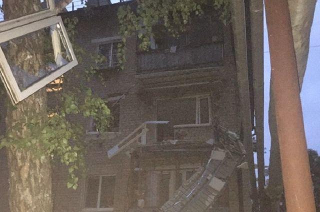 Одна из выбитых оконных конструкций повисла на дереве.