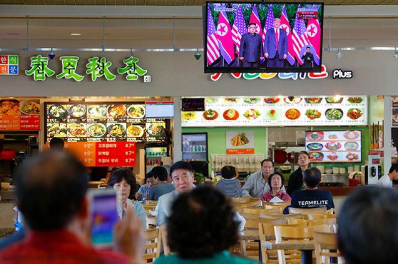 Посетители торгового центра в Лос-Анджелесе наблюдают за встречей лидеров США и КНДР.