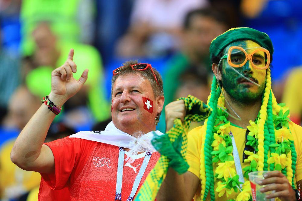 Болельщики сборных Бразилии и Швейцарии с национальной символикой на лицах и в руках.