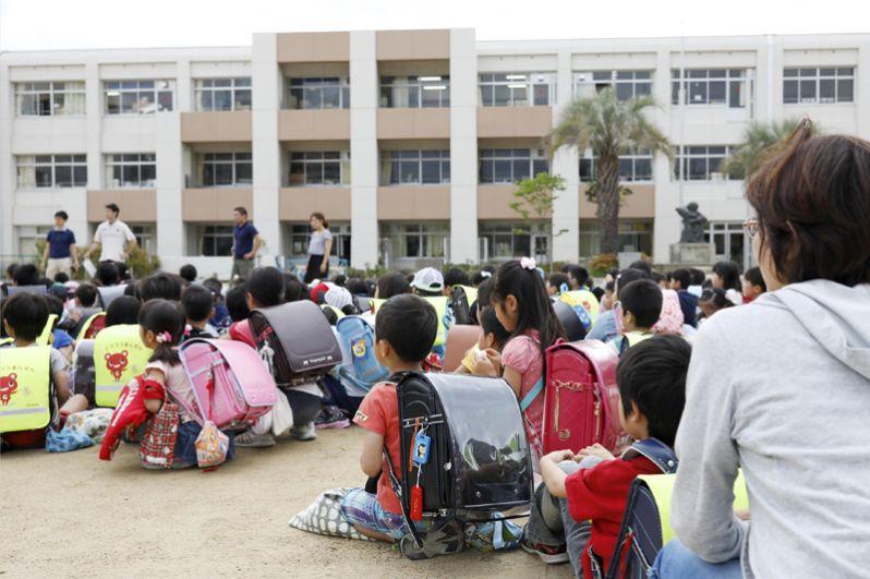 Школьники, эвакуированные из здания во время землетрясения в Икеда.