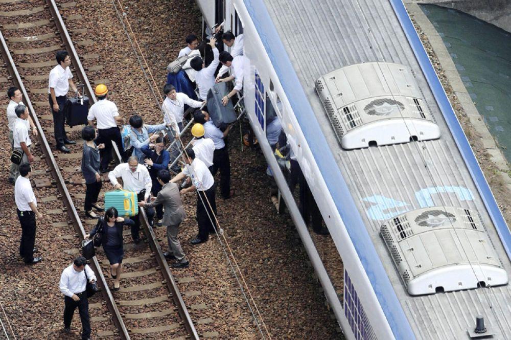 Пассажиры сходят с поезда, движение которого была приостановлено после землетрясения в Такацуки.