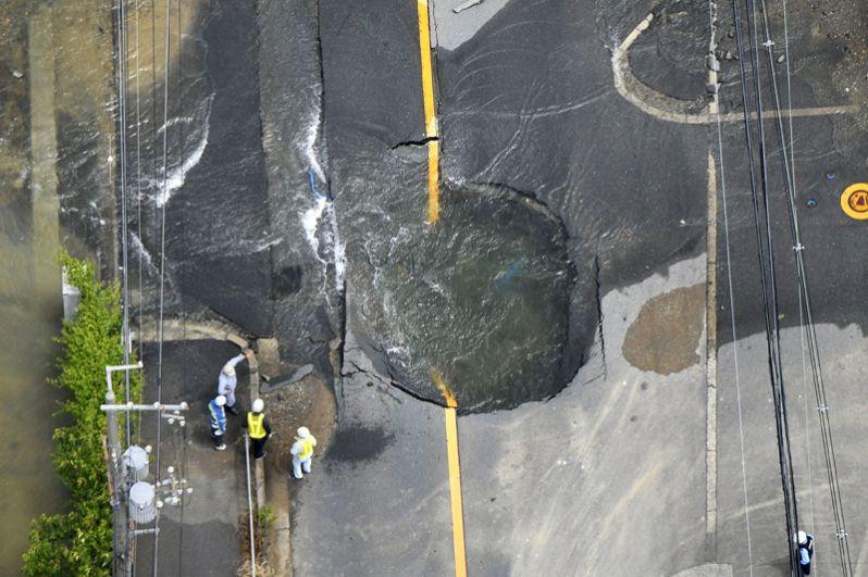 Трещины на дороге после землетрясения, заполненные водой, так как были повреждены водопроводные трубы, Такацуки.