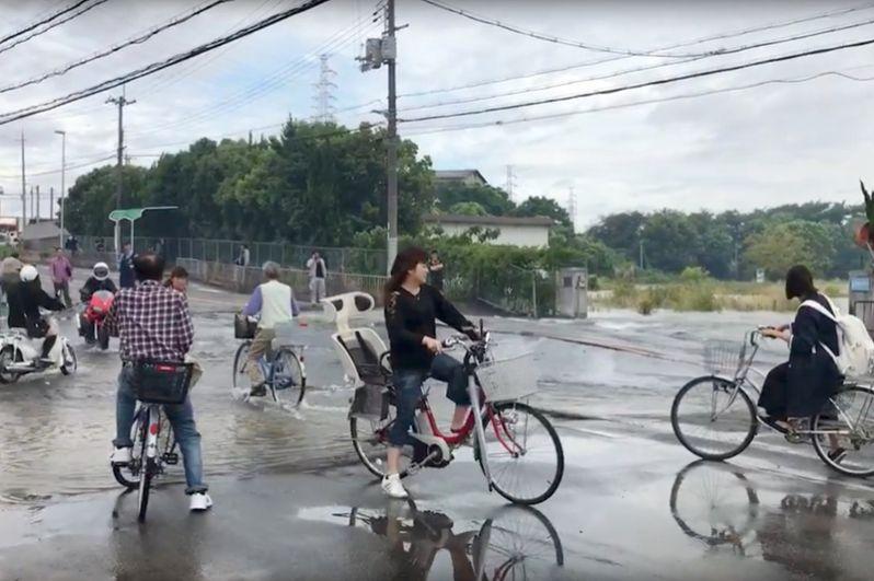 Велосипедисты на затопленной после землетрясения дороге в Осаке.