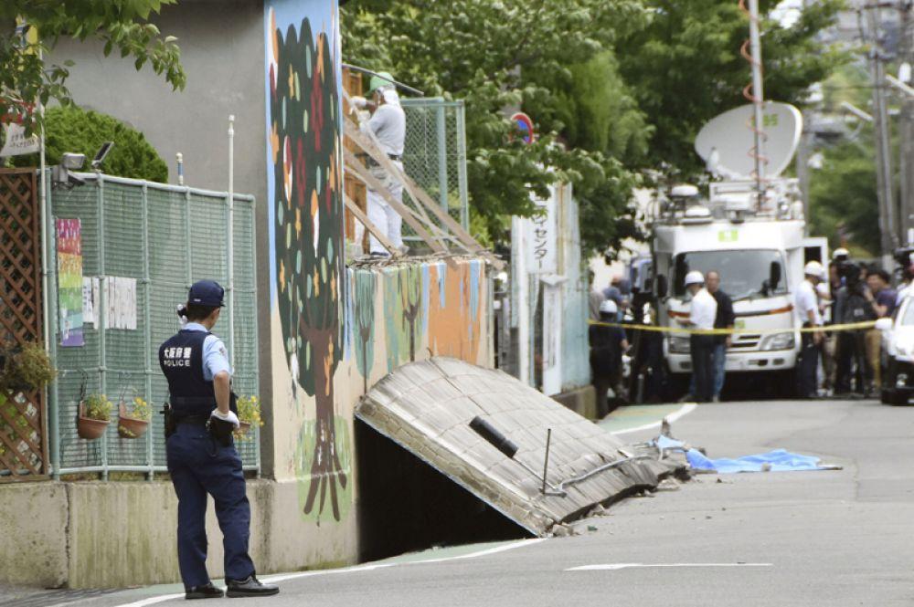 Полицейский на месте, где погибла девочка в результате падения стены в начальной школе в Такацуки.