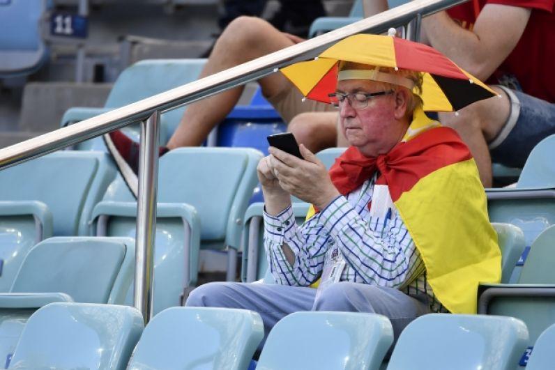 Практичный пожилой болельщик из Бельгии с зонтиком на головном уборе.