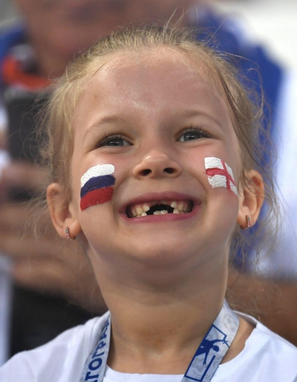 Юная болельщица с российским триколором и английским флагом на щеках.