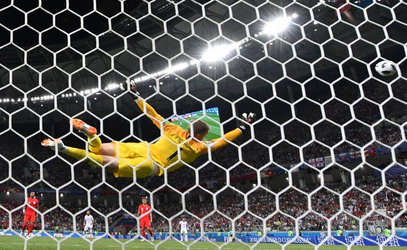 Голкипер сборной Англии Джордан Пикфорд пытается защитить ворота.
