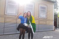 Бразильские болельщицы на фоне бутафорского баннера, имитирующего красивый фасад.