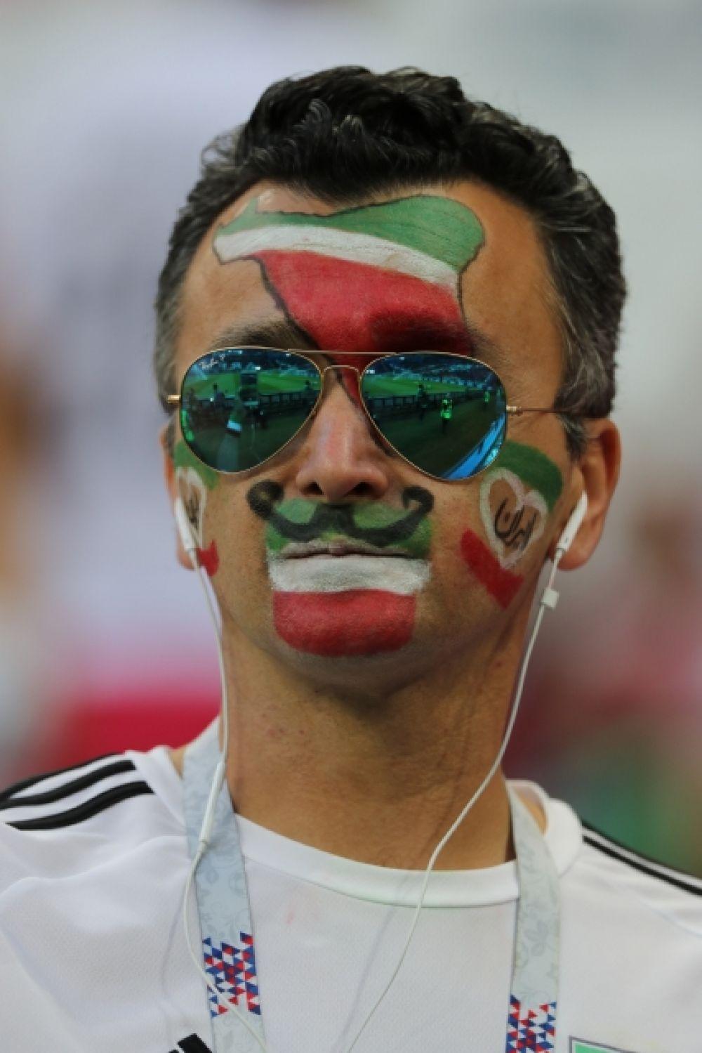 Фанат из Ирана с символикой страны на лице.