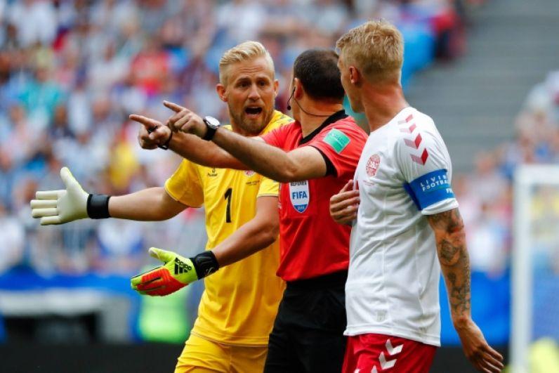 Вратарь сборной Дании Каспер Шмейхель обсуждает с судьей назначенный его команде штрафной.