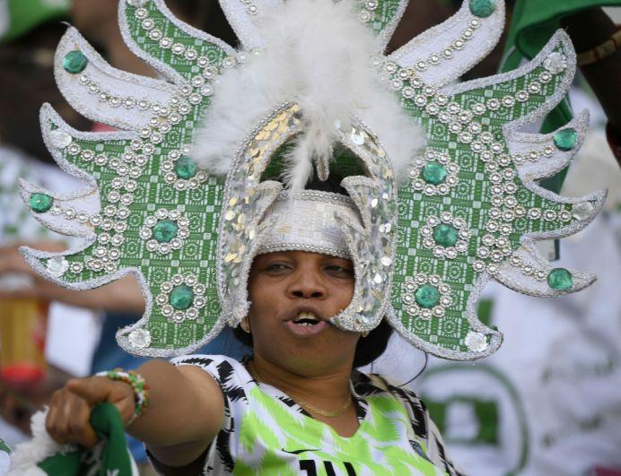 Болельщица Нигерии в головном уборе с камнями, перьями и пайетками.