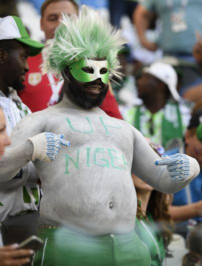 Эксцентричный нигерийский болельщик в карнавальной маске и парике цветов флага его государства.