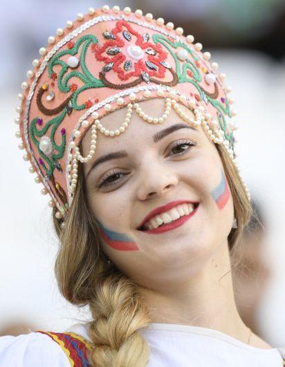 Улыбчивая болельщица с кокошником на голове и российском триколором на щеках.
