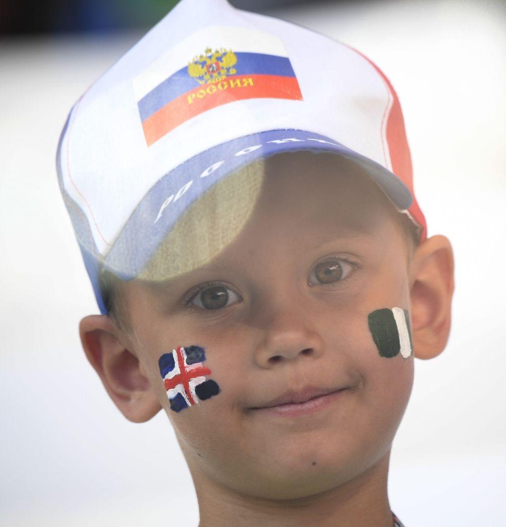 Юный фанат с флагами Исландии и Нигерии на лице.