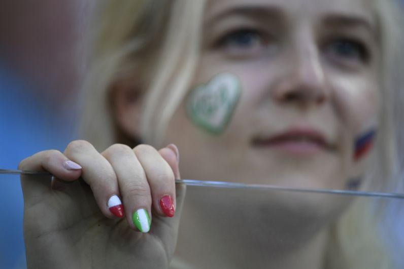 Болельщица с российским триколором и сердцем в цветах Нигерии на щеках, а также с футбольным маникюром.