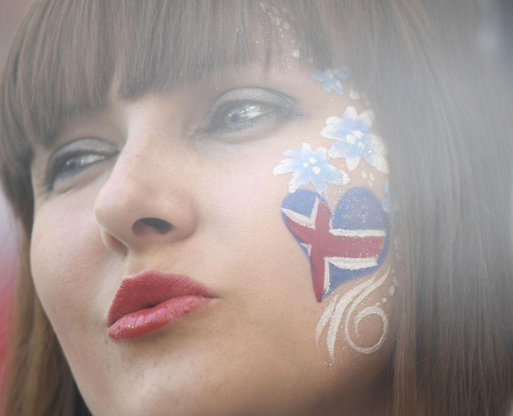 Болельщица исландской сборной с сердцем на щеке расцветки ее национального флага.