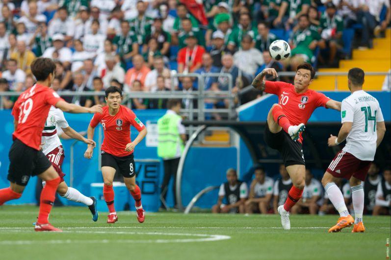 Защитник сборной Южной Кореи Хьюн Су Джанг с мячом.