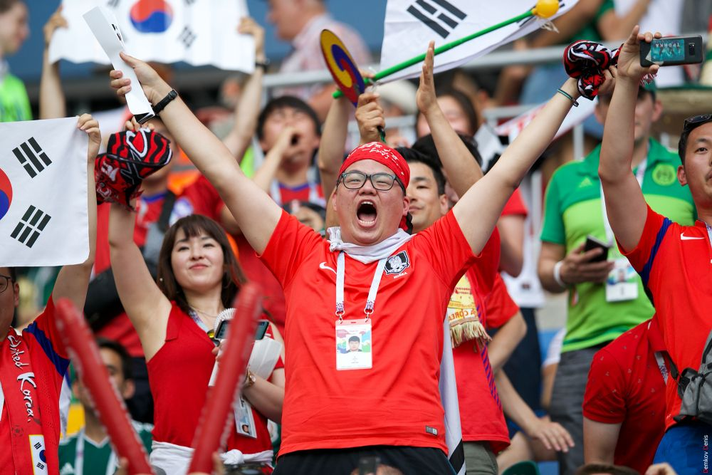 Группа южнокорейских фанатов на трибунах.