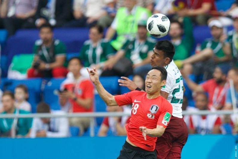 Полузащитник Сон Мин Мун отбивает мяч головой.