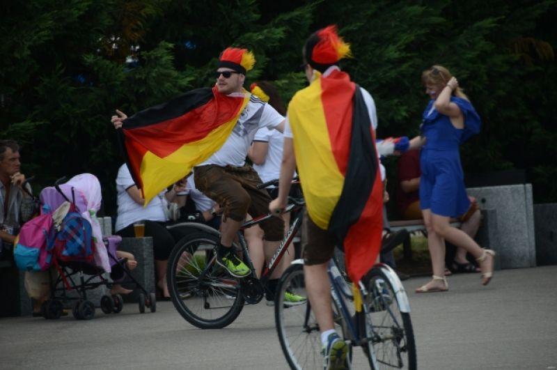Болельщики сборной Германии, завернувшись в флаги, катаются на велосипедах.